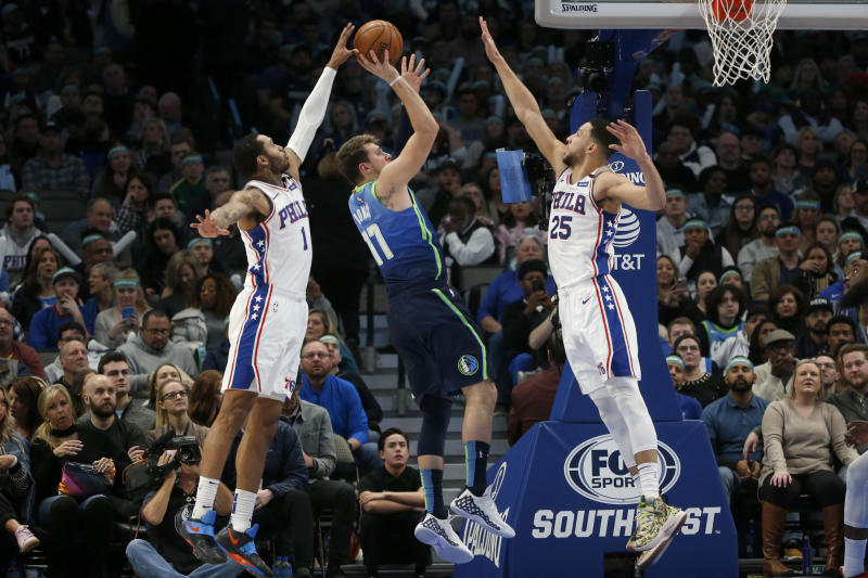 Philadelphia 76ers forward Mike Scott (1) blocks a shot by Dallas Mavericks forward Luka Doncic (77) as 76ers guard Ben Simmons (25) defends during the first half of an NBA basketball game in Dallas, Saturday, Jan 11, 2020. (AP Photo/Michael Ainsworth)