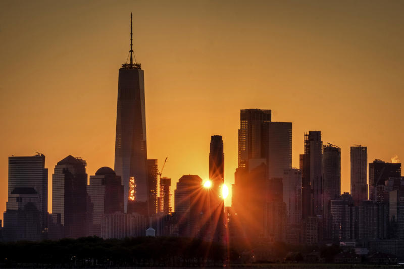 FILE - In this July 1, 2019, file photo the sunlight flares around the buildings in lower Manhattan as the sun rises in New York. Despite a decade-plus of economic growth, Americans have slowed the pace at which they're forming new companies, a trend that risks further widening the gap between the most affluent and everyone else. (AP Photo/J. David Ake, File)