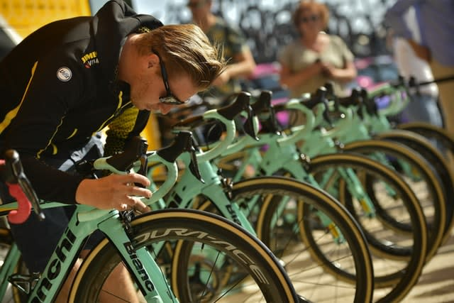 A member of Team Jumbo-Visma's staff checks the brake of a bicycle during the 14th stage of the Vuelta a Espana (Alvaro Barrientos/AP)
