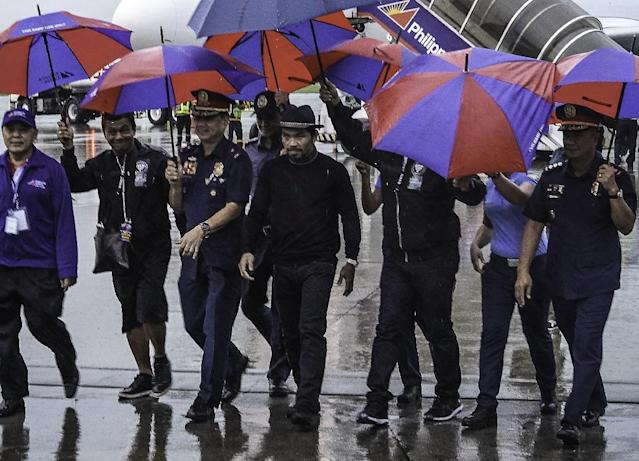 Pacquiao (C) on the tarmac after arriving from Malaysia at General Santos airport (AFP Photo/FERDINANDH CABRERA)
