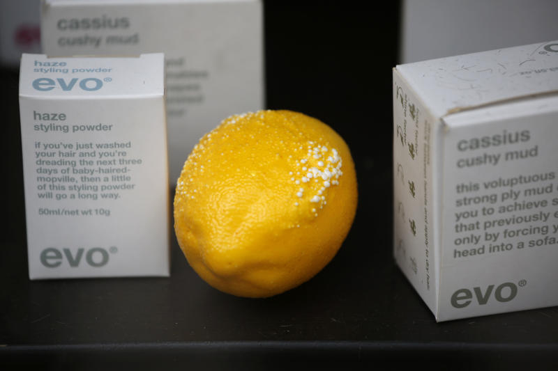 """A lemon, with blistering from the sun, is seen in the window of a gentlemen's grooming shop across the street from the 37-storey skyscraper at 20 Fenchurch Street in the City of London, which is still under construction, Tuesday, Sept. 3, 2013. Developers for an unfinished skyscraper in central London say they are investigating the way the building reflects bright sunlight _ after claims that the intense glare melted parts of a car parked nearby. The companies behind the skyscraper, nicknamed the """"Walkie-Talkie"""" because of its curved shape, are responding to complaints from the owner of a Jaguar who told the BBC that the mirror, panels and the Jaguar badge had all melted from the concentrated heat of sunlight reflected from the building. (AP Photo/Matt Dunham)"""