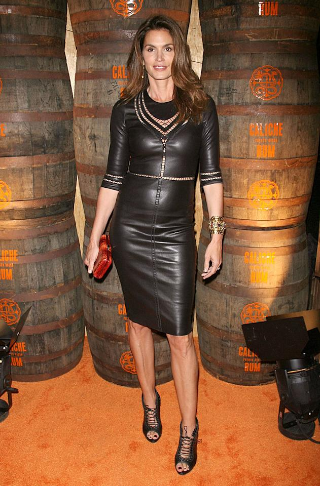 "Despite the fact that Cindy Crawford began modeling 30 years ago, the 46-year-old mom-of-two still has what it takes to turn heads. At the recent Caliche Rum launch party in NYC, Crawford showed off her money-making looks in a curve-hugging leather frock, which featured cut-out panels around the neckline, midriff, and sleeves. A chic gold cuff, red clutch, and lace-up peep-toes completed the supermodel's sexy ensemble. (5/22/2012)<br><br><a target=""_blank"" href=""http://bit.ly/lifeontheMlist"">Follow 2 Hot 2 Handle creator, Matt Whitfield, on Twitter!</a>"