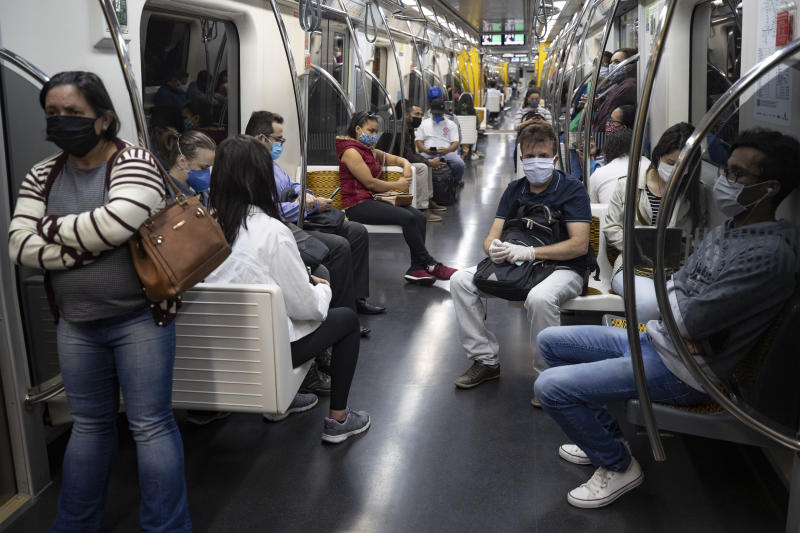 Commuters wear face masks on the subway amid the spread of the new coronavirus in Sao Paulo, Brazil, Monday, May 4, 2020. The state government said starting Monday masks are mandatory on public transportation. (AP Photo/Andre Penner)