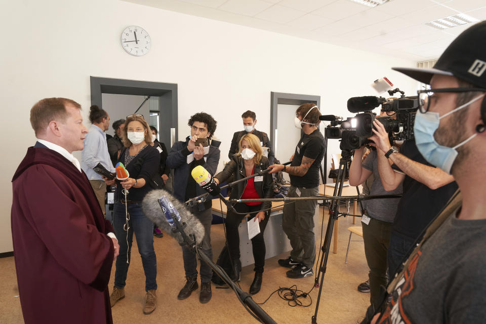 Senior public prosecutor Jasper Klinge, left, talks to journalists at the Koblenz court building after the end of today's trial in Koblenz, Germany, Thursday, April 23, 2020. Two former members of Syria's secret police go on trial Thursday in Germany accused of crimes against humanity for their role in a government-run detention center where large numbers of opposition protesters were tortured.(Thomas Frey/dpa via AP)