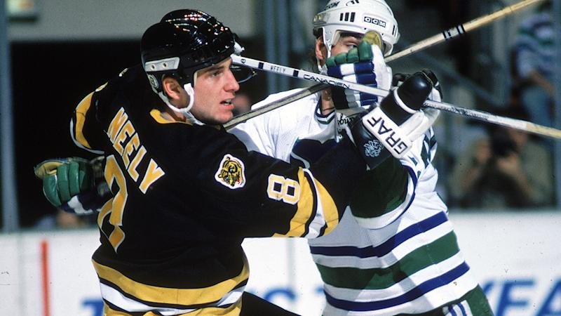 Cam Neely of the Boston Bruins, pictured here crossing sticks with Scot Kleinendorst.