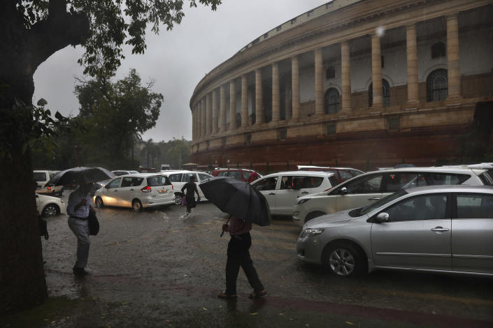 Lawmakers arrive amidst heavy downpour at the Parliament House in New Delhi, India, Tuesday, Aug. 6, 2019. India's lower house of Parliament was set to ratify a bill that would downgrade the governance of India-administered, Muslim-majority Kashmir. (AP Photo/Manish Swarup)