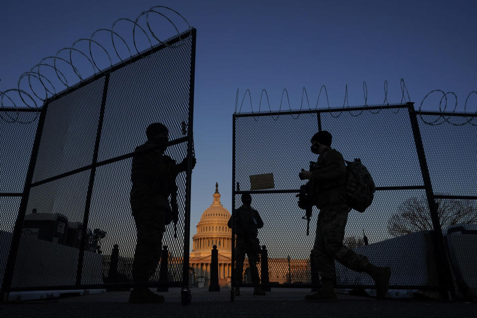 National Guard open a gate in the razor wire topped perimeter fence around the Capitol allow another member in at sunrise in Washington, Monday, March 8, 2021. (AP Photo/Carolyn Kaster)