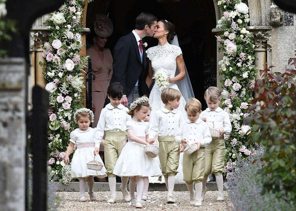 """<p>Pippa Middleton and James Matthews kiss beneath an arch of flowers at St Mark's Church after <a href=""""https://www.townandcountrymag.com/the-scene/weddings/g9899242/pippa-middleton-wedding-pictures/"""" rel=""""nofollow noopener"""" target=""""_blank"""" data-ylk=""""slk:their wedding ceremony"""" class=""""link rapid-noclick-resp"""">their wedding ceremony</a>. Leading the procession are their page boys and bridesmaids, including Prince George and Princess Charlotte. </p>"""