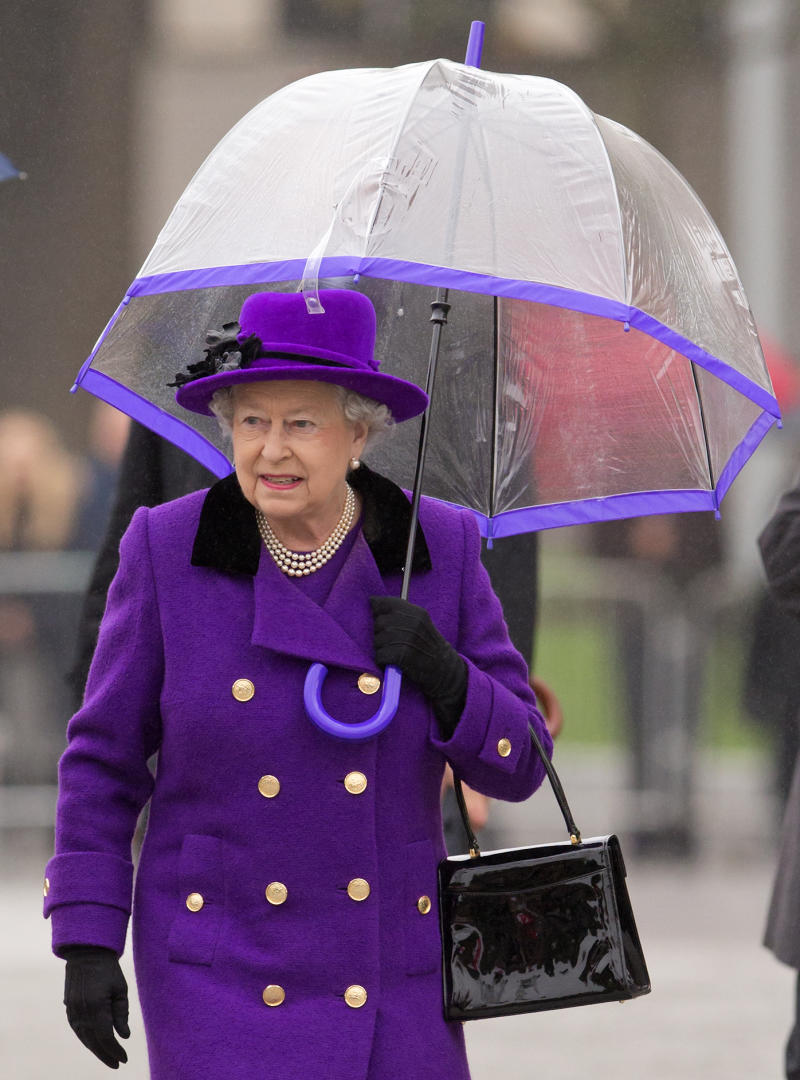LONDON, UNITED KINGDOM - OCTOBER 25: (EMBARGOED FOR PUBLICATION IN UK NEWSPAPERS UNTIL 48 HOURS AFTER CREATE DATE AND TIME) Queen Elizabeth II shelters under an umbrella as attends the opening of the newly developed Jubilee Gardens on October 25, 2012 in London, England. (Photo by Indigo/Getty Images)