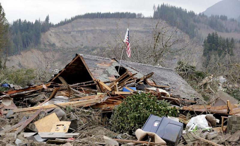 A flag sticks out of a hole in a demolished home near where a deadly mudslide from the hill behind that happened several days earlier ended, Tuesday, March 25, 2014, in Arlington, Wash. At least 14 people were killed in the 1-square-mile slide that hit in a rural area about 55 miles northeast of Seattle on Saturday. Several people also were critically injured, and homes were destroyed. (AP Photo/Elaine Thompson)