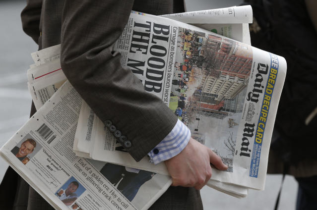 A man carries newspapers featuring the Boston marathon blasts on the front page, while waiting to cross a road in central London, Tuesday, April 16, 2013. British police are reviewing security plans for Sunday's London Marathon, the next major international marathon, because of the bombs that killed three people at the marathon in Boston Monday. (AP Photo/Sang Tan)