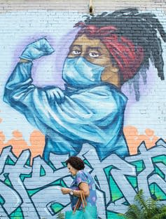 A woman walks by a street mural of a health-care worker in protective equipment, flexing her bicep