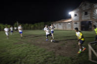 Friar Leopoldo Serrano shoots for a goal while playing soccer with seminarians and residents at his drug rehab center in Mission San Francisco de Asis, Honduras, Monday, June 21, 2021. Since moving to the mission in 2009, Serrano has preached the Bible, organized protest marches against violence, negotiated drug-free events such as soccer matches, and promoted religious celebrations and social work. (AP Photo/Rodrigo Abd)
