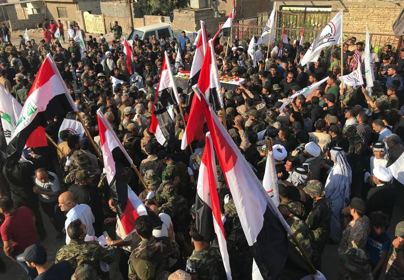 Mourners carry the coffin of Abu Ali al-Dabi, a fighter of the Popular Mobilization Forces killed in a drone attack, during his funeral procession in Baghdad, Iraq, Monday, Aug. 26, 2019. Two unidentified drones killed two Iraqi members of an Iran-backed paramilitary force on Sunday, the group said in a statement, saying the attack took place in Iraq near the border with Syria. (AP Photo/Ali Abdul Hassan)