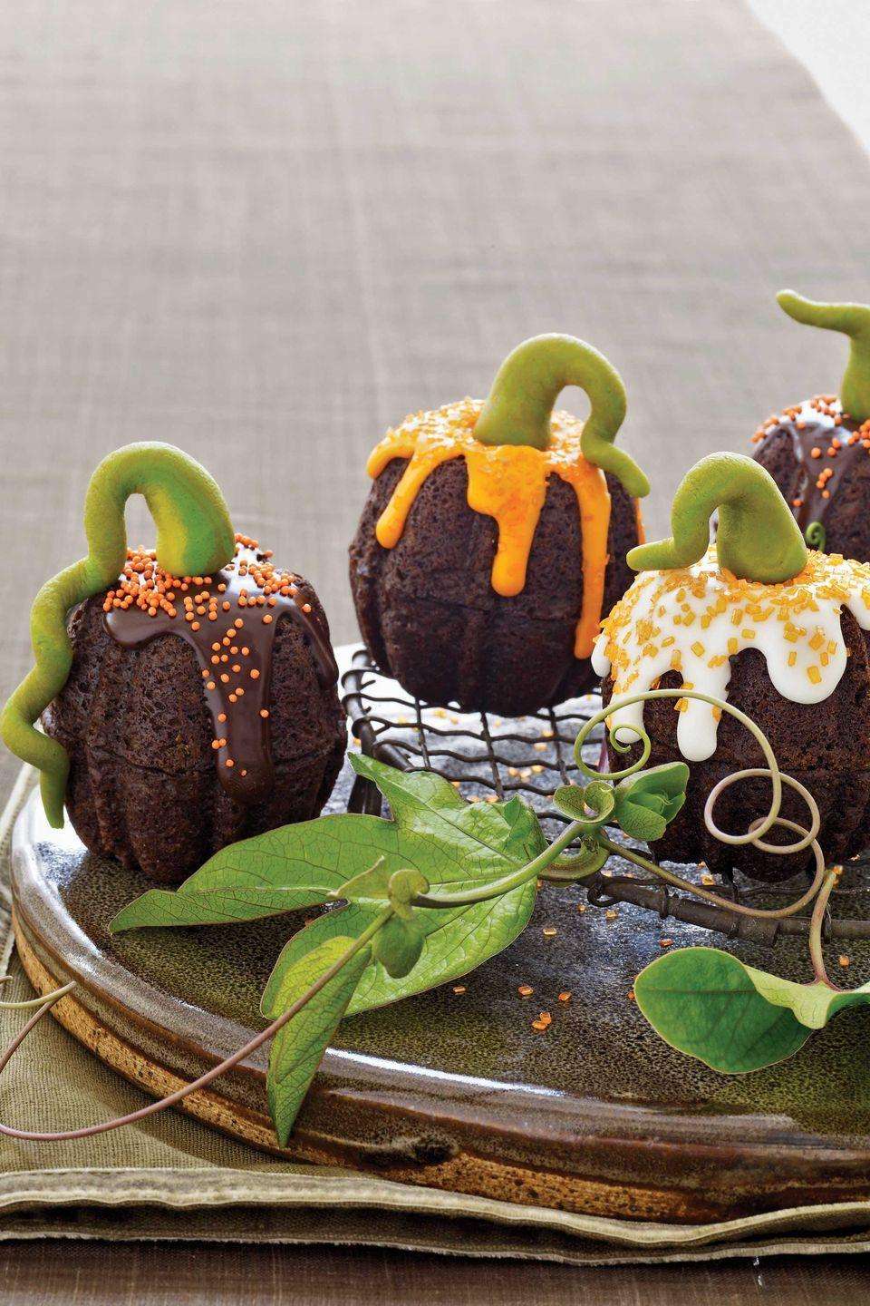 """<p>To make this luscious dessert, use our simple Classic Chocolate Cake recipe. You can also try substituting your favorite cake recipe, or if you're short on time, a boxed mix — one box yields 12 Mini Pumpkin Cakes, or two 8-inch-round layers. </p><p> To get the look of these single-serving pumpkin treats, trim the bottoms of cakes baked in mini Bundt pans to create a flat surface. Join two cakes so that the fluted tops are at either end, then drizzle with chocolate or vanilla glaze and sprinkle with coarse colored sugar or nonpareils before the glaze sets. Top with a marzipan stem. Read the marzipan instructions at <a href=""""https://www.countryliving.com/food-drinks/g617/marzipan-pumpkin-stems-1008/"""" rel=""""nofollow noopener"""" target=""""_blank"""" data-ylk=""""slk:Marzipan Pumpkin Stems"""" class=""""link rapid-noclick-resp"""">Marzipan Pumpkin Stems</a>.</p><p><strong><a href=""""https://www.countryliving.com/food-drinks/recipes/a2422/classic-chocolate-cake/"""" rel=""""nofollow noopener"""" target=""""_blank"""" data-ylk=""""slk:Get chocolate cake recipe"""" class=""""link rapid-noclick-resp"""">Get chocolate cake recipe</a>.</strong></p><p><a class=""""link rapid-noclick-resp"""" href=""""https://www.amazon.com/Wilton-2105-445-Mini-Fluted-Small/dp/B0000DIX7S?tag=syn-yahoo-20&ascsubtag=%5Bartid%7C10050.g.1366%5Bsrc%7Cyahoo-us"""" rel=""""nofollow noopener"""" target=""""_blank"""" data-ylk=""""slk:SHOP MINI BUNDT PANS"""">SHOP MINI BUNDT PANS </a></p>"""