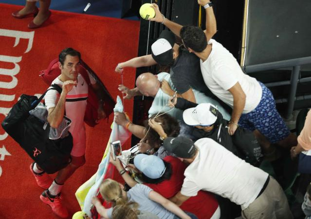 Tennis - Australian Open - Rod Laver Arena, Melbourne, Australia, January 20, 2018. Roger Federer of Switzerland throws a pen into the crowd as he signs autographs after winning against Richard Gasquet of France. REUTERS/Edgar Su