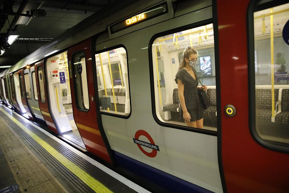 "A passenger wears a face mask as a precaution against the transmission of the novel coronavirus as she boards a London Underground tube train in London on July 17, 2020. - Boris Johnson said on July 17 he hoped Britain would ""return to normality"" by November despite being badly affected by the coronavirus and predictions of a second wave of cases during winter months. Johnson sketched out a timetable for easing the remaining lockdown measures in England, including lifting homeworking guidance and reopening sports stadiums and live theatre. (Photo by Tolga AKMEN / AFP) (Photo by TOLGA AKMEN/AFP via Getty Images)"