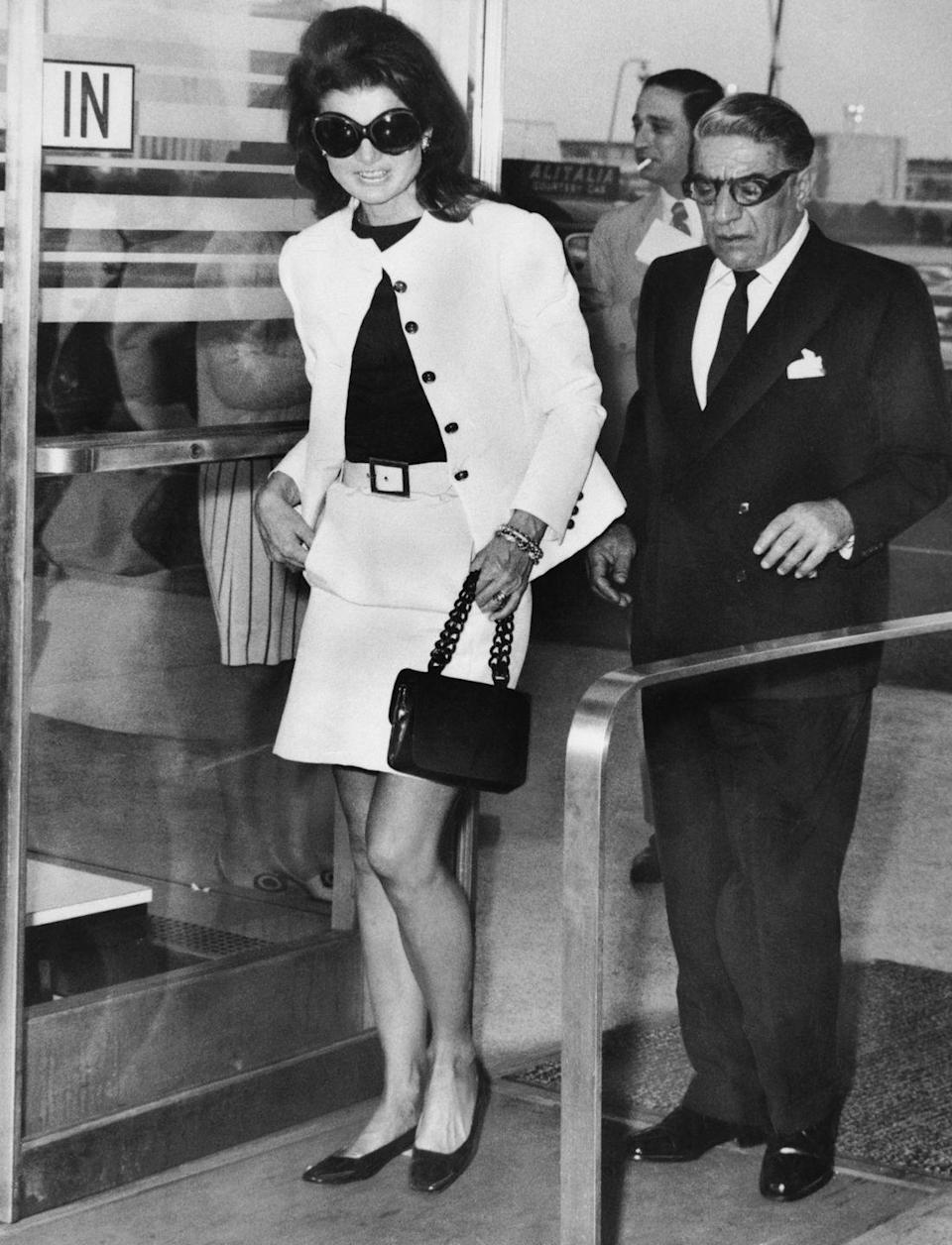 <p>A matching jacket-and-skirt set paired with a small black handbag and black leather heels make for an elegant outfit for bidding Aristotle Onassis goodbye at the Kennedy Airport.<br></p>