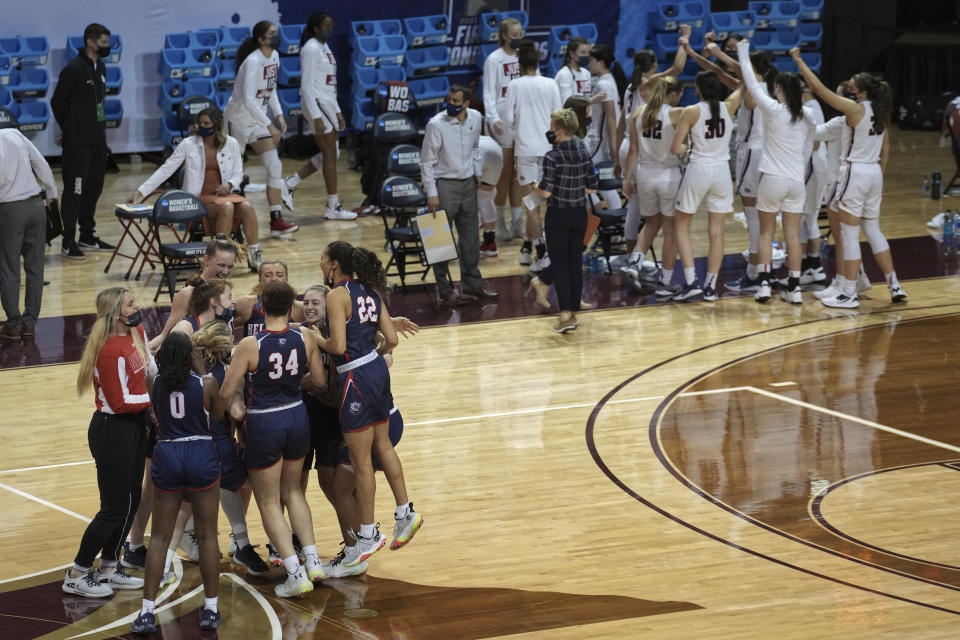 Belmont players, left, celebrate after a win over Gonzaga, background, in a college basketball game in the first round of the NCAA women's tournament at the University Events Center in San Marcos, Texas, Monday, March 22, 2021. (AP Photo/Chuck Burton)