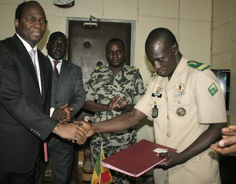 Coup leader Capt. Amadou Haya Sanogo, right, shakes hands with Burkina Faso Foreign Minister Djibrill Bassole, after signing an accord agreeing to return the country to constitutional rule, in Sanogo's office at junta headquarters in Kati, outside Bamako, Mali Friday, April 6, 2012. Under intense pressure from the nations bordering Mali, Sanogo, the junior officer who seized control of the country in a coup last month signed an accord agreeing to return the country to constitutional rule. The announcement was made late Friday, only hours after separatist rebels in the country's distant north declared their independence. (AP Photo/Harouna Traore)