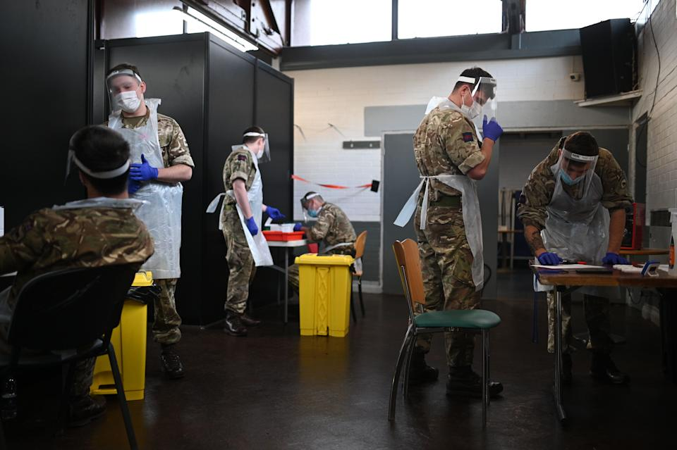 British Army soldiers, 1st battalion Coldstream Guards, staff a coronavirus testing centre set up at the Merseyside Caribbean Council Community Centre in Liverpool, north west England, on November 10, 2020 during a city-wide mass testing pilot operation. - Liverpool on November 6 began England's first city-wide trial of coronavirus testing in an attempt to prevent hospitals becoming overwhelmed during the country's second wave of the pandemic. All of the northwestern city's 500,000 residents as well as people working there will be offered repeat tests, even if asymptomatic, under the pilot trial, which will initially run for two weeks. (Photo by Oli SCARFF / AFP) (Photo by OLI SCARFF/AFP via Getty Images)