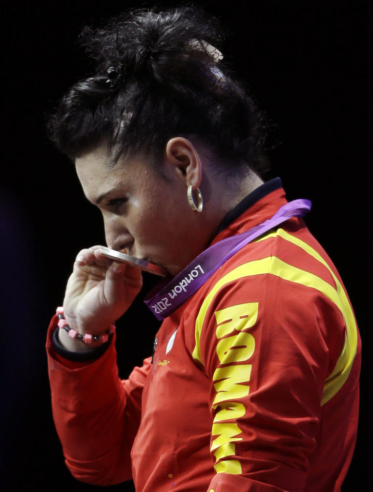 Silver medalist Roxana Daniela Cocos of Romania kisses her medal during a medals  ceremony after the women's 69-kg weightlifting competition at the 2012 Summer Olympics, Wednesday, Aug. 1, 2012, in London. (AP Photo/Mike Groll)