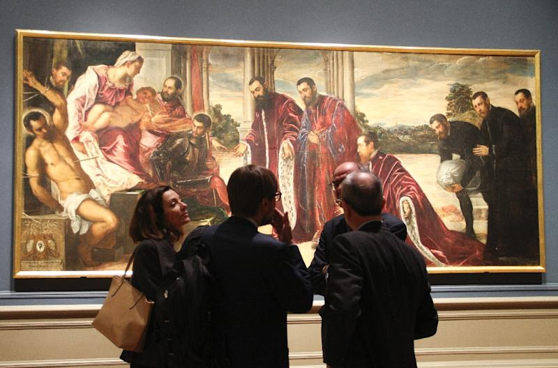 "A group of people stands in front of Tintoretto's painting ""The Madonna of the Treasurers"" (1567) (AFP Photo/Olivia Hampton)"