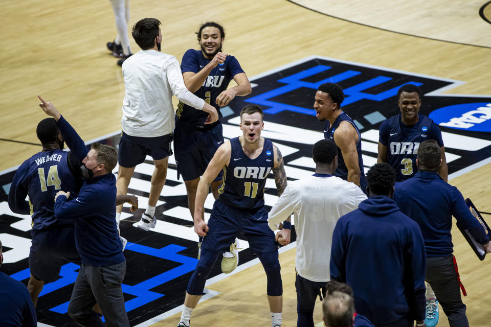 Oral Roberts players and coaches celebrate after beating Ohio State in a first-round game in the NCAA men's college basketball tournament, Friday, March 19, 2021, at Mackey Arena in West Lafayette, Ind. (AP Photo/Robert Franklin)