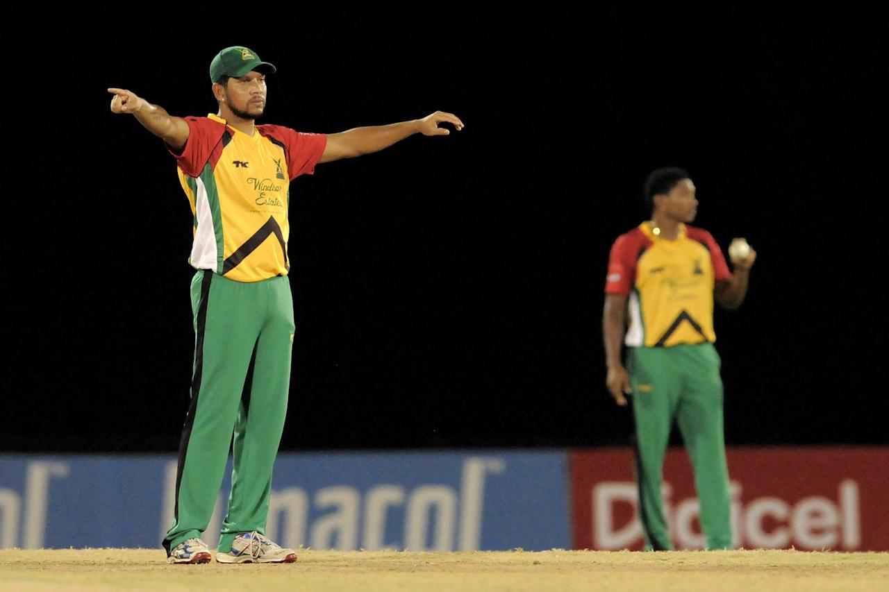 PORT OF SPAIN, TRINIDAD AND TOBAGO - AUGUST 24:  Captain Ramnaresh Sarwan of Guyana Amazon Warriors sets the field for Krishmar Santokie (R) during the Final of the Caribbean Premier League between Guyana Amazon Warriors v Jamaica Tallawahs at Queens Park Oval on August 24, 2013 in Port of Spain, Trinidad and Tobago. (Photo by Randy Brooks/Getty Images Latin America for CPL)