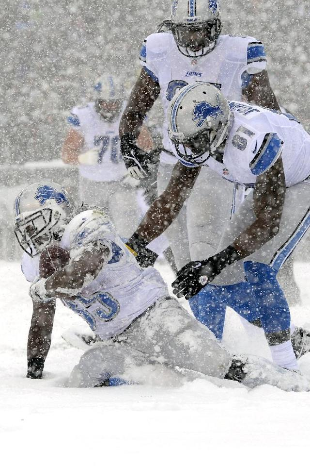 Detroit Lions' Joique Bell, left, gets up with the help of Brandon Pettigrew, center, and Calvin Johnson after scoring a touchdown during the first half of an NFL football game against the Philadelphia Eagles, Sunday, Dec. 8, 2013, in Philadelphia. (AP Photo/Michael Perez)