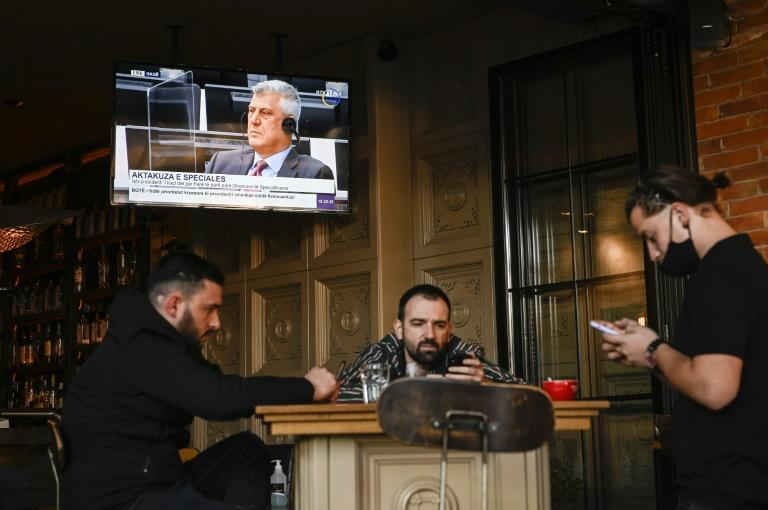 Men in a coffee bar in Pristina look at their mobile phones rather than a TV broadcast of war crimes proceedigns in The Hague against Kosovo's former president Hashim Thaci.