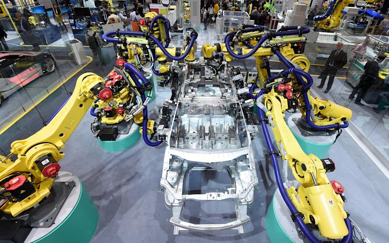 Robots simulating the production of a car at the stand of exhibitor Fanuc at the robotics fair Automatica in Munich, Germany, 21 June 2016. The fair is open until 24 June 2016. PHOTO: TOBIAS HASE/dpa | usage worldwide (Photo by Tobias Hase/picture alliance via Getty Images)