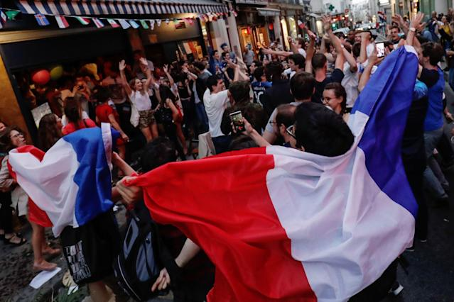 <p>People celebrate France's victory outside a cafe in central Paris on July 10, 2018 at the final whistle at the Russia 2018 World Cup semi-final football match between France and Belgium. (Photo by Thomas SAMSON / AFP) </p>