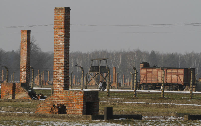 """This image taken Jan 28. 2011 shows people walking  through the Nazi death camp Auschwitz-Birkenau in Oswiecim, Poland.  The red brick barracks that housed starving inmates are sinking into ruin. Time has warped victims' leather shoes into strange shapes. Hair sheared to make cloth is slowly turning to dust. Officials  launched a global campaign to raise euro120 million ($165 million) to create a """"perpetual fund"""" whose interest can be drawn on indefinitely to repair barracks, watchtowers, crematoria and other structures at the Auschwitz-Birkenau state museum and memorial in southern Poland. (AP Photo/Czarek Sokolowski)"""