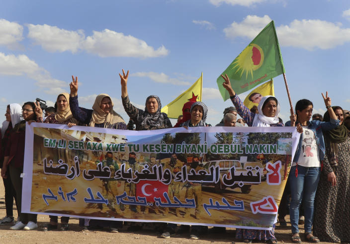"""Kurdish women hold a banner with Arabic that read, """"We don't accept enemies and strangers on our land,"""" as they protest against possible Turkish military operation on their areas, at the Syrian-Turkish border, in Ras al-Ayn, Syria, Monday, Oct. 7, 2019. Syria's Kurds accused the U.S. of turning its back on its allies and risking gains made in the fight against the Islamic State group as American troops began pulling back on Monday from positions in northeastern Syria ahead of an expected Turkish assault. (AP Photo)"""
