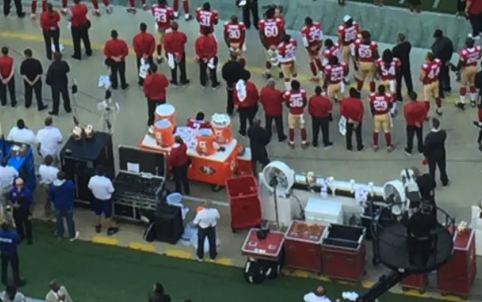 NFL quarter-back Colin Kaepernick (pictured centre), sat down as everyone else stood on 26 August, 2016, in a gesture which would go on to inspire a global movement. (Twitter/Jennifer Lee Chan/SB Nation)