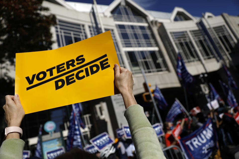 A demonstrator calling for all votes to be counted holds up a sign toward protesting supporters of President Donald Trump outside the Pennsylvania Convention Center, Thursday, Nov. 5, 2020, in Philadelphia, as vote counting in the general election continues. (AP Photo/Rebecca Blackwell)