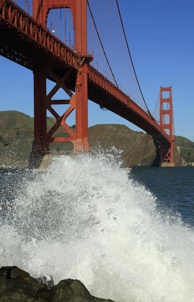 A wave breaks under the Golden Gate Bridge at high tide Thursday, Dec. 13, 2012 in San Francisco. The National Weather Service says so-called King Tides — caused by a rather unique combination of how the sun, the moon and the earth align — will bring the highest tides of the year on Thursday, Friday and Saturday mornings. Along with the high tides, forecasters say a building swell will bring large breaking waves to area beaches. The San Francisco Chronicle reports the combination of high tides and surf has flooded some parking lots in San Francisco and in Marin County. (AP Photo/Ben Margot)