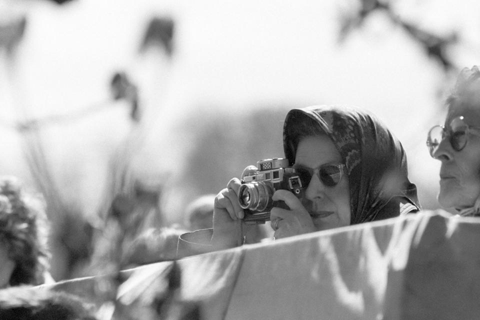 <p>The Queen takes a picture at the Badminton Horse Trials. (PA Archive) </p>