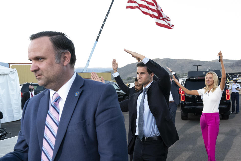 """In this Oct. 18. 2020 photo, White House social media director Dan Scavino, left, Director of the White House Presidential Personnel Office John McEntee, and White House press secretary Kayleigh McEnany, watch and dance as President Donald Trump departs after speaking at a campaign rally at Carson City Airport, in Carson City, Nev. President Donald Trump, a man who is famously particular about his appearance, is fully embracing doing a dad dance to the Village People's """"YMCA"""" as the finale to his rallies in the campaign's closing stretch.(AP Photo/Alex Brandon)"""