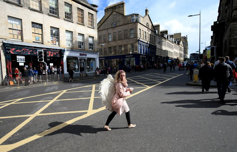 FILE PHOTO: A woman wearing angel wings crosses a road during the fringe festival in Edinburgh
