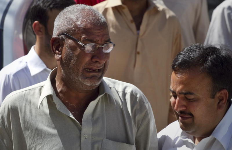 A man comforts the brother of Pakistani prosecutor Chaudhry Zulfikar who was assassinated hours earlier, outside his residence in Islamabad, Pakistan, Friday, May 3, 2013. Gunmen killed Pakistan's lead prosecutor investigating the assassination of former prime minister Benazir Bhutto as he drove to court in the capital on Friday, throwing the case that also involves former ruler Pervez Musharraf into disarray. (AP Photo/Anjum Naveed)