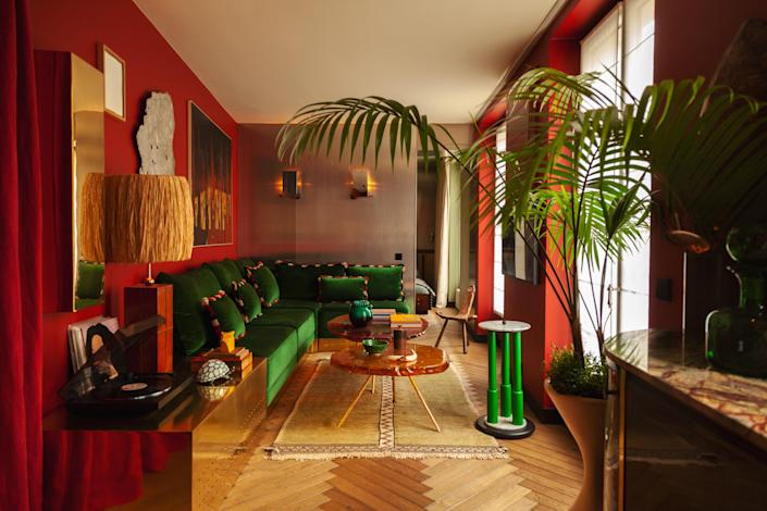 The main living space features pieces from different styles and eras, such as the sofa designed by Hugo with a Pierre Frey velvet fabric, sconces by Gio Ponti, a coffee table by Hélène de Saint Lager, a Moroccan rug, a Memphis-style green table in marble from the '80s, and a surrealist painting by Andrée Pollier.