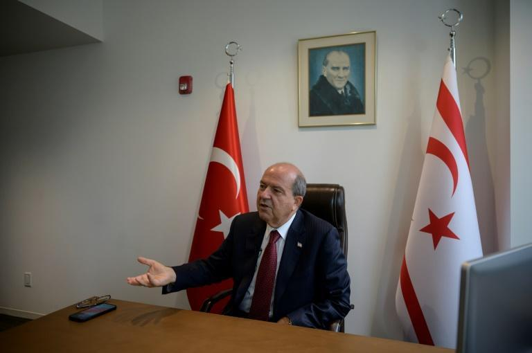 Turkish Cypriot leader Ersin Tatar sits beneath a portrait of the founder of modern Turkey, Kemal Ataturk, as he speaks with AFP in his office at the Turkish Center near the United Nations (AFP/Ed JONES)