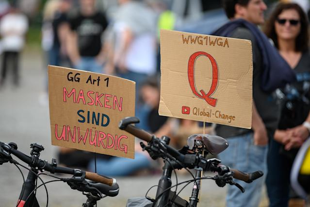Signs referencing the QAnon conspiracy theory, which originated in the U.S., are displayed at a demonstration protesting coronavirus quarantine measures in Stuttgart, Germany. (Sebastian Gollnow/picture alliance via Getty Images)