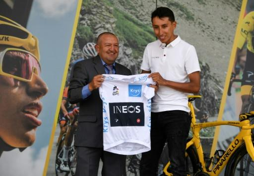 Colombia's Tour de France winner Egan Bernal (right) donates his white jersey for best young rider to his first cycling trainer Fabio Rodriguez