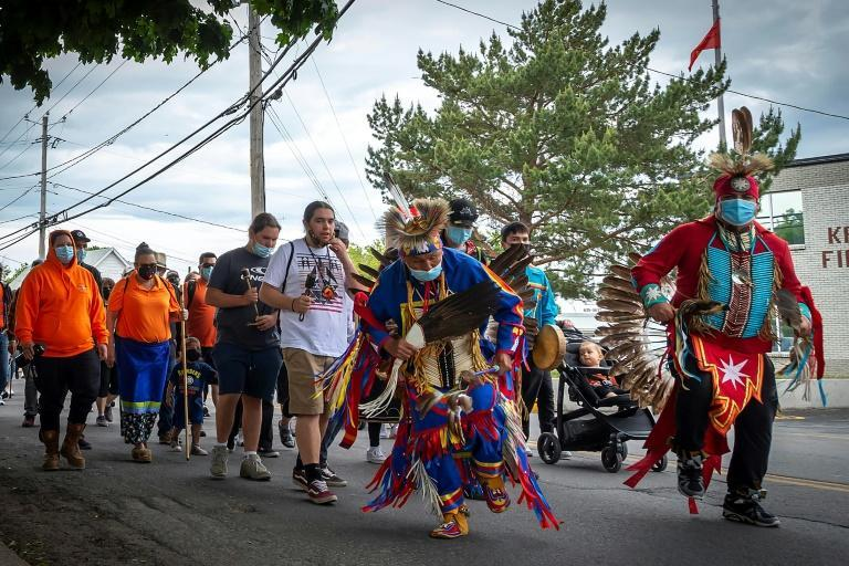 Members of the community of the Kahnawake Mohawk Territory, Quebec march through the town on May 30, 2021, to commemorate the news that a mass grave of 215 Indigenous children were found at the Kamloops Residential School in British Columbia, Canada