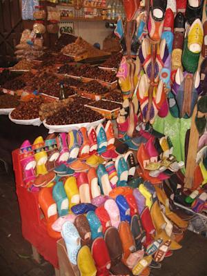 two traditional Moroccan products -- dates and leather slippers -- for sale