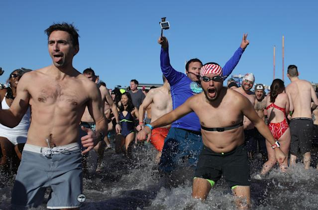 <p>Participants rush in the water during a polar bear plunge at the beach in Coney Island, Brooklyn on Jan. 1, 2018. New Yorkers took part in new year's day swim with temperature standing at -7 degrees Celsius. (Photo: Atilgan Ozdil/Anadolu Agency/Getty Images) </p>