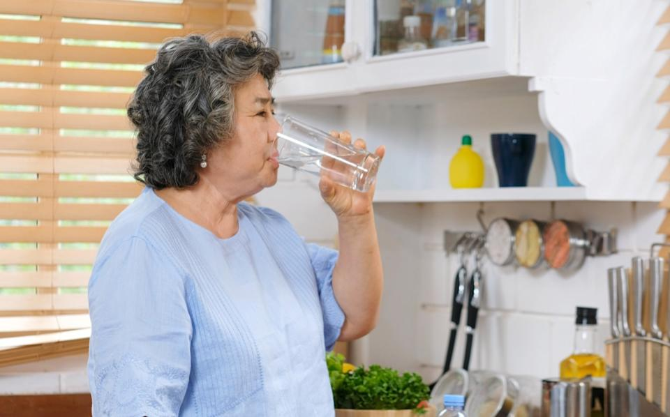 Older Asian woman drinking water in the kitchen